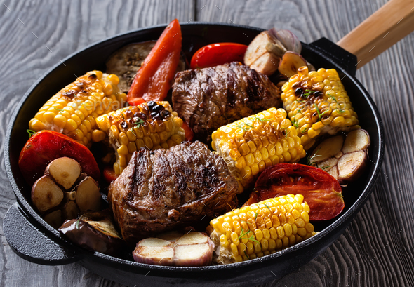 Fried meat and vegetables on a cast-iron frying pan - Stock Photo - Images