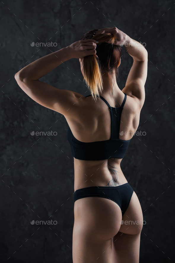 Young fitness girl getting prepared for the workout isolated on dark background - Stock Photo - Images