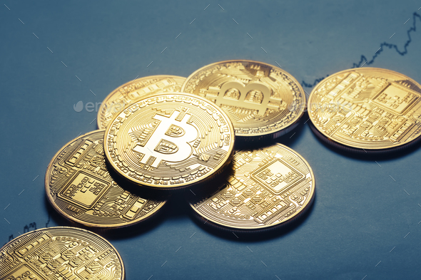 Virtual currency bitcoin lies on paper with a growing graph - Stock Photo - Images