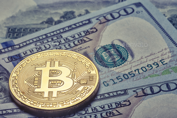 Golden shiny bitcoin on the background of one hundred dollar bil - Stock Photo - Images