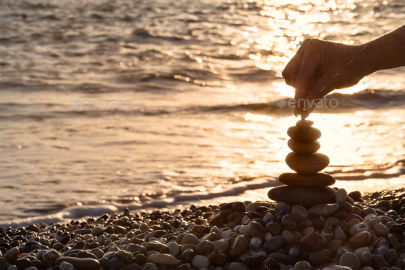 Female hand setting pebble to the top of pyramid - Stock Photo - Images