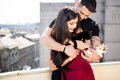 Young couple holding cats in hands on the terrace