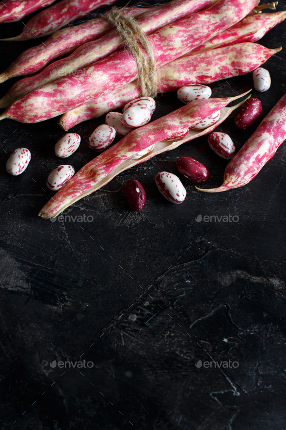 Pinto beans with pods on a wooden table - Stock Photo - Images