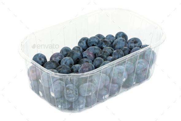 Blueberries in a plastic container on white background - Stock Photo - Images