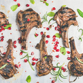 Slow food dinner with grilled lamb ribs and pomegranate, herbs