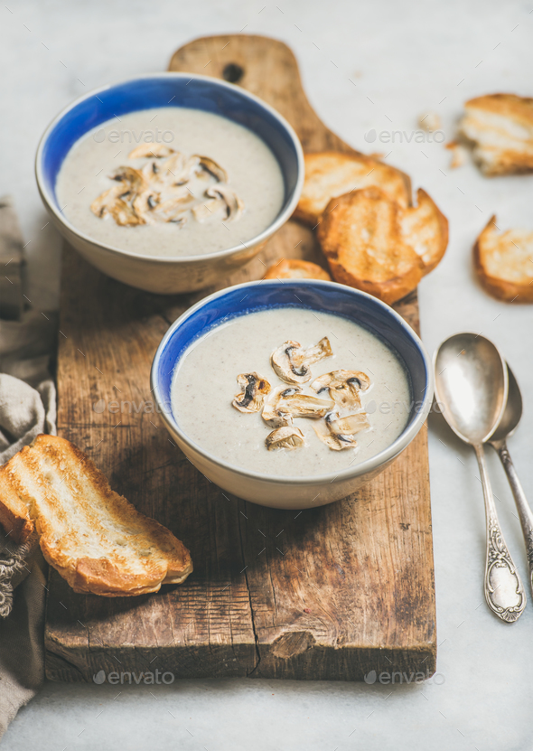 Creamy mushroom soup in bowls with grilled bread slices - Stock Photo - Images