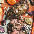 Cooked Roastbeef meat with vegetables and herbs in baking tray
