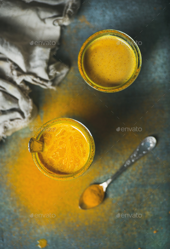 Golden milk with turmeric powder in glasses over dark background - Stock Photo - Images