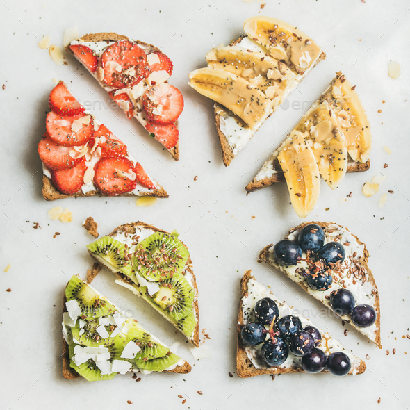 Healthy toasts with cream-cheese, fruit, nuts and seeds, square crop - Stock Photo - Images