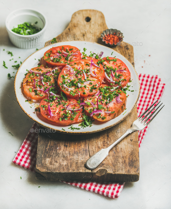 Fresh heirloom tomato, parsley and onion salad. Vegetarian food concept - Stock Photo - Images