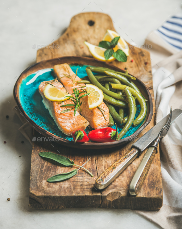 Roasted salmon fish with lemon, rosemary, chilli pepper and beans - Stock Photo - Images