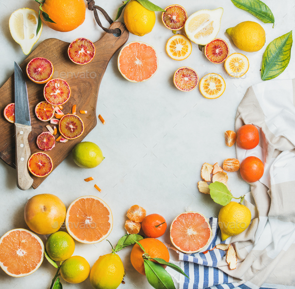 Citrus fruits slices over grey marble background, top view - Stock Photo - Images