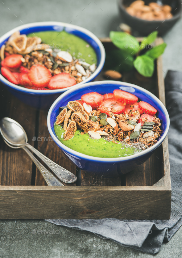 Green smoothie bowls with seeds, nuts, fruit and fresh berries - Stock Photo - Images