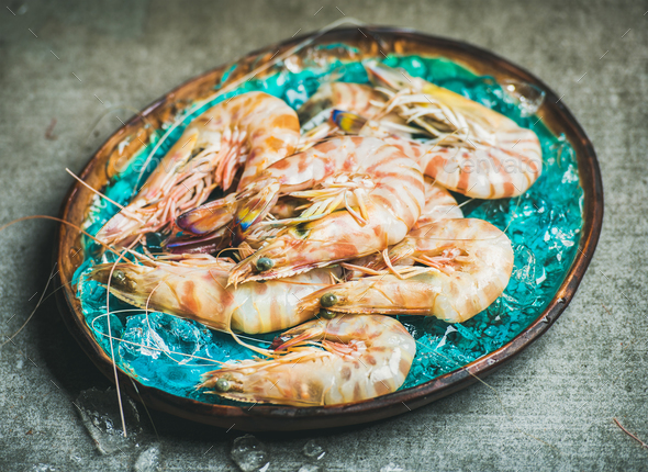 Raw uncooked tiger prawns on chipped ice, concrete background - Stock Photo - Images