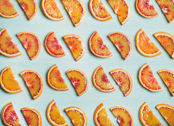 Fresh juicy blood orange slices over blue painted table background - Stock Photo - Images
