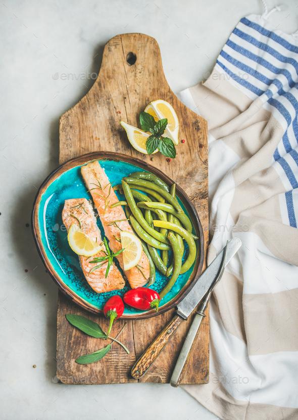 Roasted salmon fillet with lemon, rosemary, chilli pepper, green beans - Stock Photo - Images
