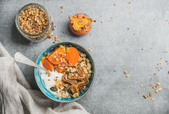 Oatmeal, quinoa gluten-free granola, yogurt, dried fruit, seeds, honey, persimmon - Stock Photo - Images
