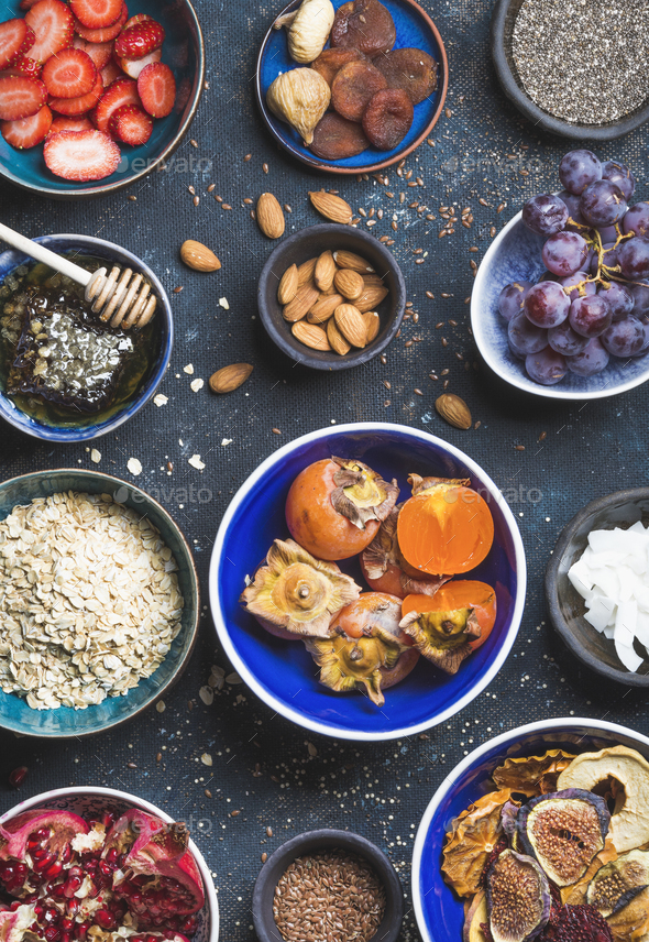 Ingredients in bowls for healthy breakfast over dark blue background - Stock Photo - Images