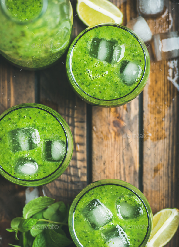 Fresh green smoothie with ice cubes in rustic wooden tray - Stock Photo - Images