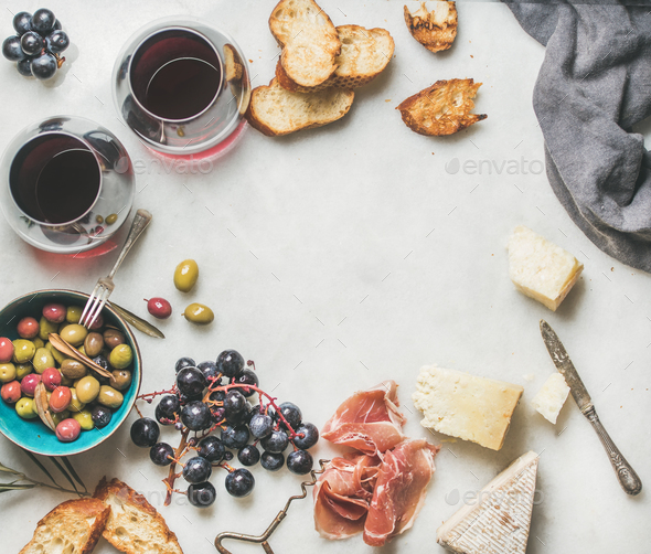 Cheese, olives, grapes, prosciutto, grilled baguette and red wine - Stock Photo - Images