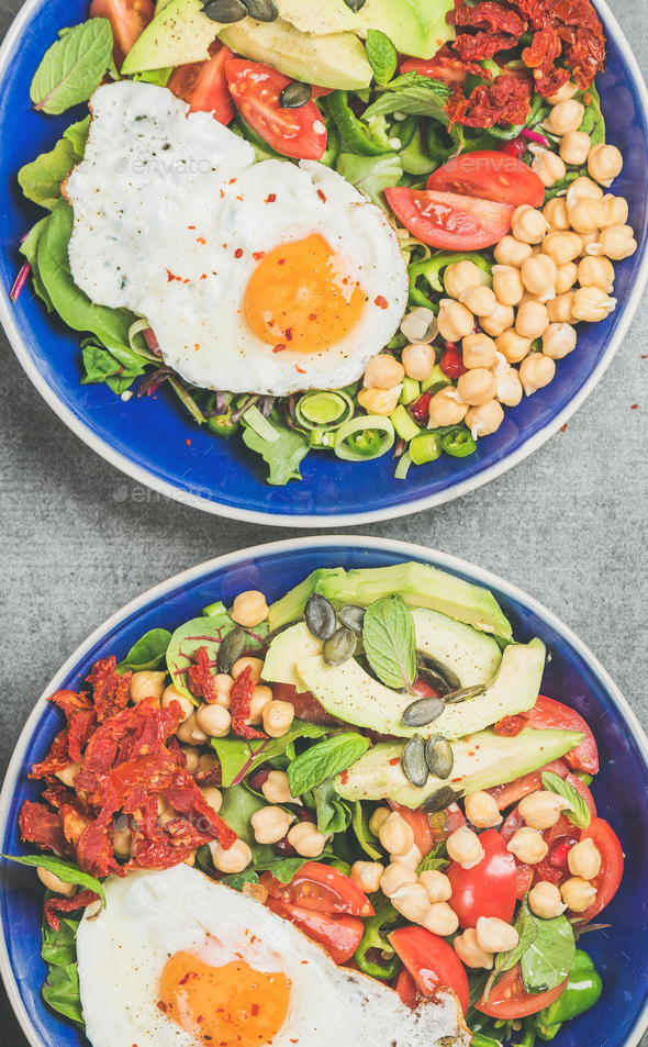 Close-up of breakfast with fried egg, chickpea, vegetables, seeds, greens - Stock Photo - Images