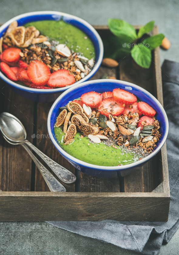 Green smoothie breakfast bowls with seeds, nuts, fruit and berries - Stock Photo - Images
