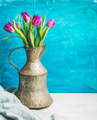 Spring purple tulips in vintage rustic copper jug, blue background