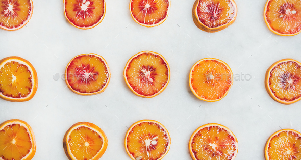 Fresh juicy blood orange slices over light marble table background - Stock Photo - Images