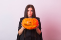 Gothic young woman in witch halloween costume with a carved pumpkin - PhotoDune Item for Sale