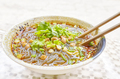 Spicy noodle soup with vegetables, herbs, peanuts and coriander.