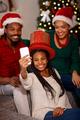 afro American family in Santa hats taking selfie on Christmas
