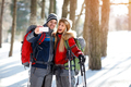Male and female hikers taking photos on winter in wood