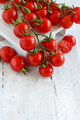 Cherry tomatoes on a white wooden tabe close up
