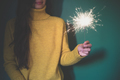 Woman having fun with a sparkler.