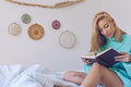 Young woman sitting in bed while reading a book - PhotoDune Item for Sale