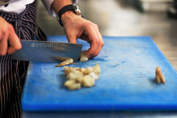 Chef is cutting raw shrimp with big special knife - Stock Photo - Images