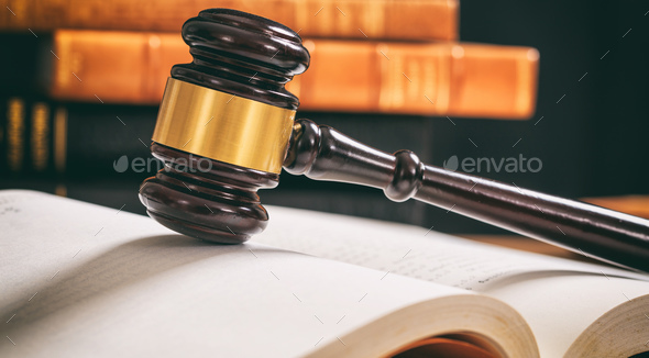 Judge gavel on an open book, wooden desk, law books background - Stock Photo - Images