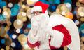 santa claus with gifts bag over christmas lights