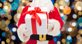 close up of santa claus with christmas gift