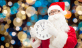 santa claus with twelve on clock at christmas