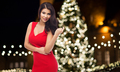 beautiful woman in red dress over christmas tree