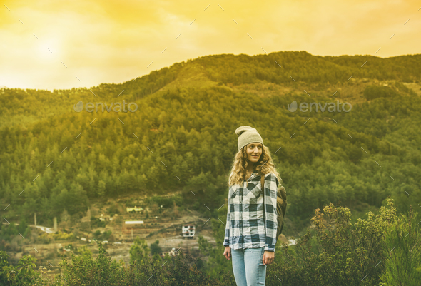 Young woman traveler in chekered shirt hiking in the mountains - Stock Photo - Images
