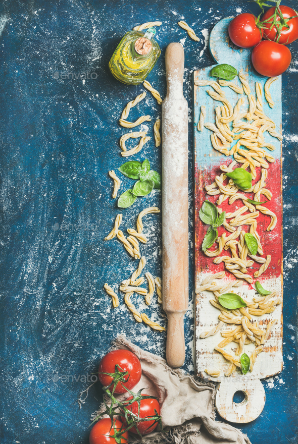 Fresh pasta casarecce, tomatoes, basil, olive oil on colorful board - Stock Photo - Images