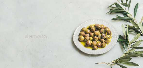 Pickled green Mediterranean olives and olive-tree branch, wide format - Stock Photo - Images