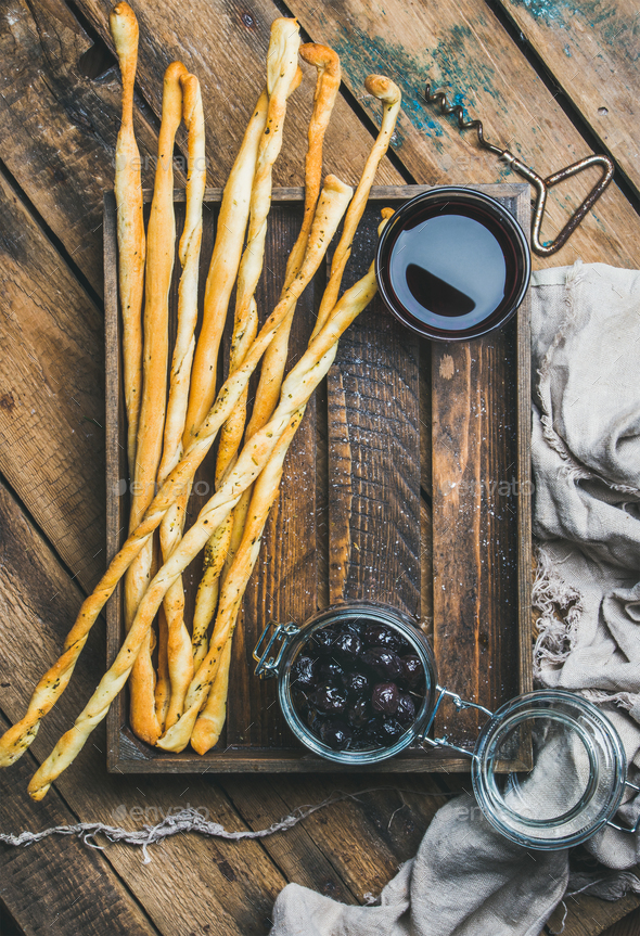 Grissini bread sticks, black olives, red wine in wooden tray - Stock Photo - Images