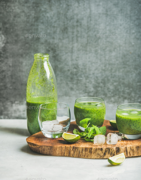 Fresh green smoothie with ice, mint and lime on board - Stock Photo - Images