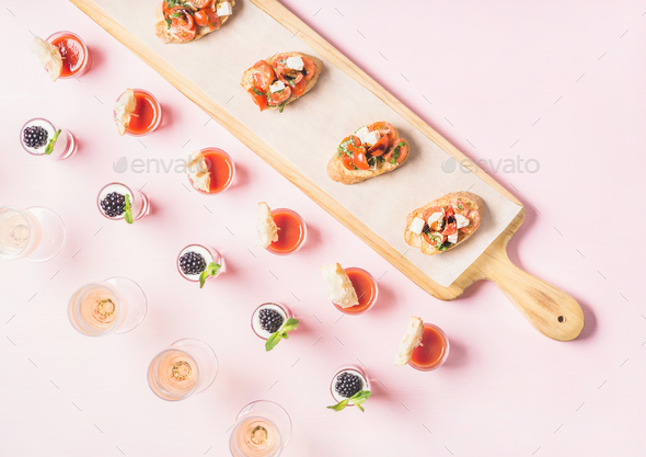 Snacks, brushetta sandwiches, gazpacho shots, desserts over pastel pink background - Stock Photo - Images