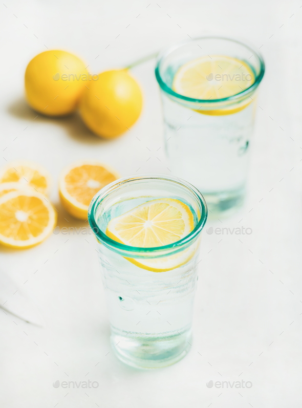 Detox lemon water in glasses served with fresh lemons - Stock Photo - Images