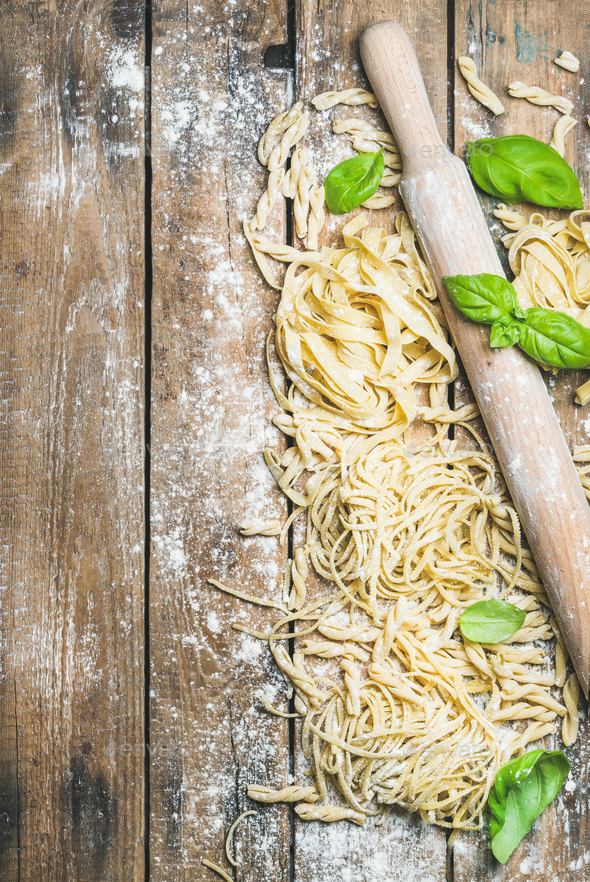 Various homemade fresh uncooked Italian pasta with flour, basil - Stock Photo - Images