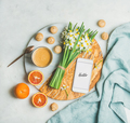 Coffee, cookies, oranges, flowers and mobile phone with word Hello